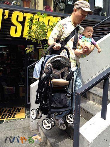 赤ちゃんを片手に抱っこしながらベビーカーを運ぶ北野啓太郎さん